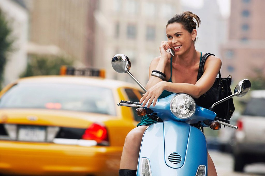 Woman using mobile phone on moped : Stock Photo