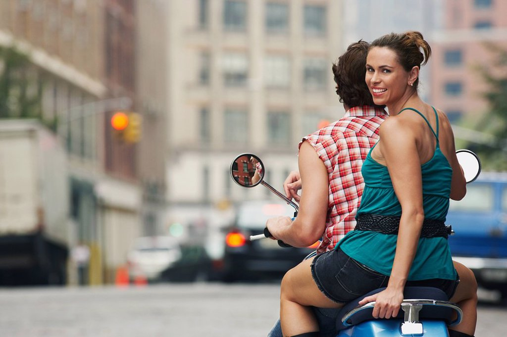 Couple riding on moped in street : Stock Photo