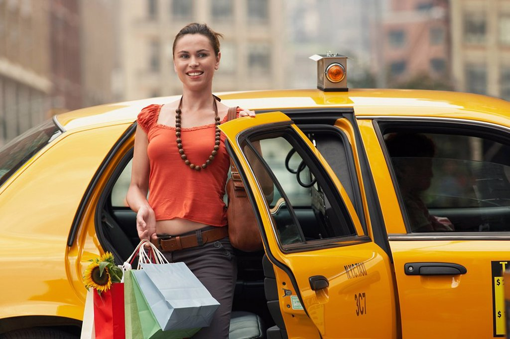 Young woman with shopping bags exiting yellow taxi cab : Stock Photo