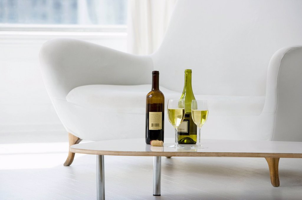 Wine glasses and bottles on coffee table in living room : Stock Photo