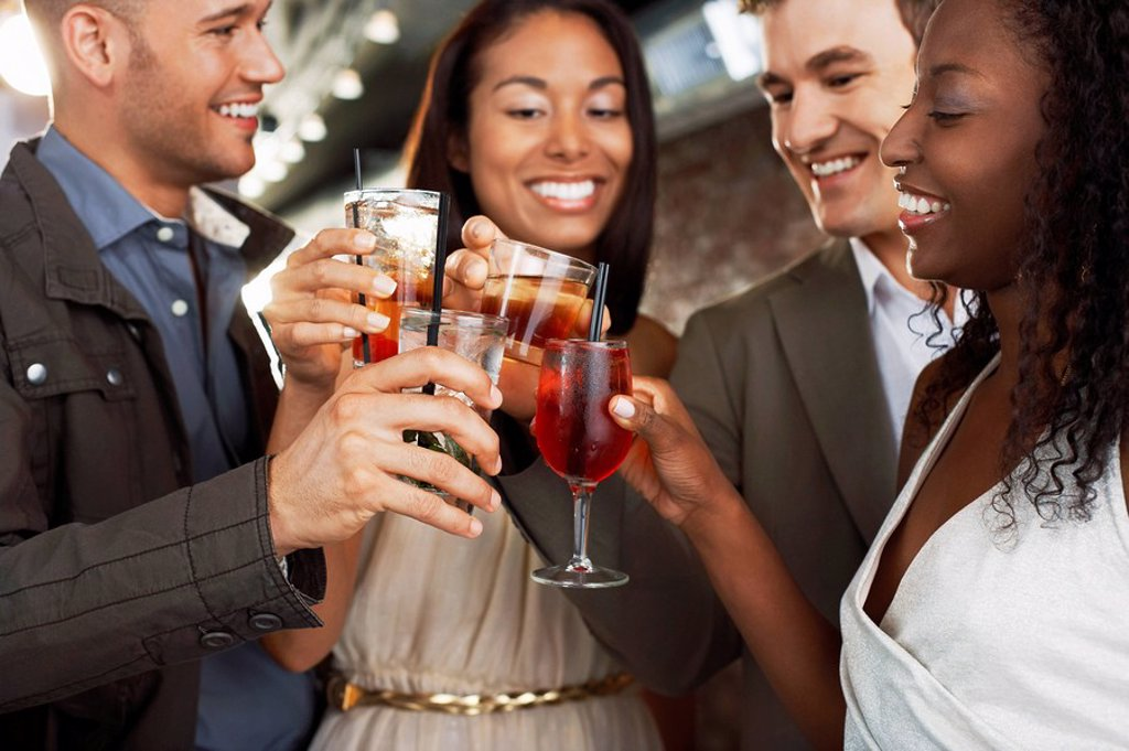 Stock Photo: 1654R-13179 Friends toasting standing at bar