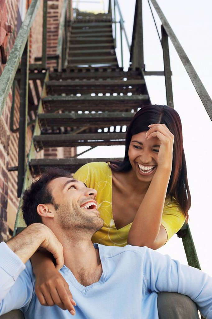 Couple sitting on fire escape stairs : Stock Photo