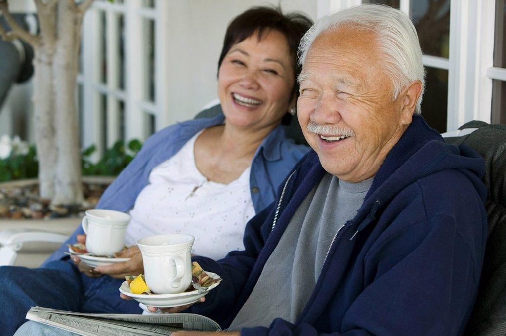 Senior couple drinking tea on porch smiling : Stock Photo