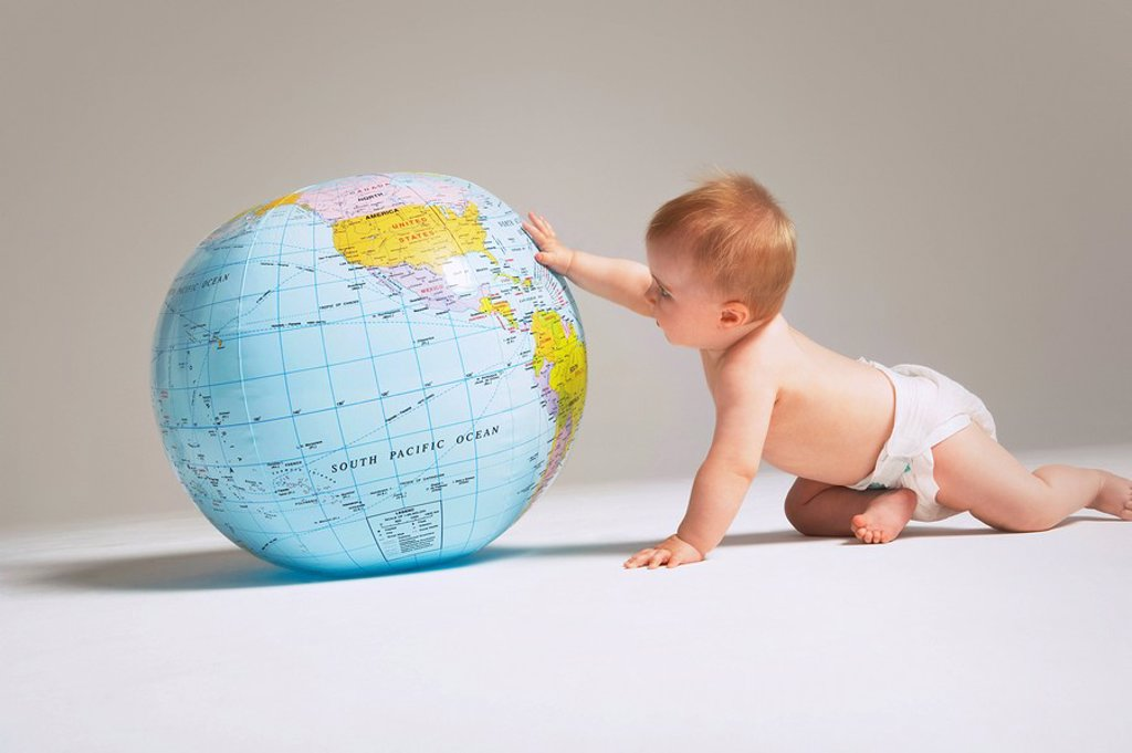Baby touching inflatable globe : Stock Photo