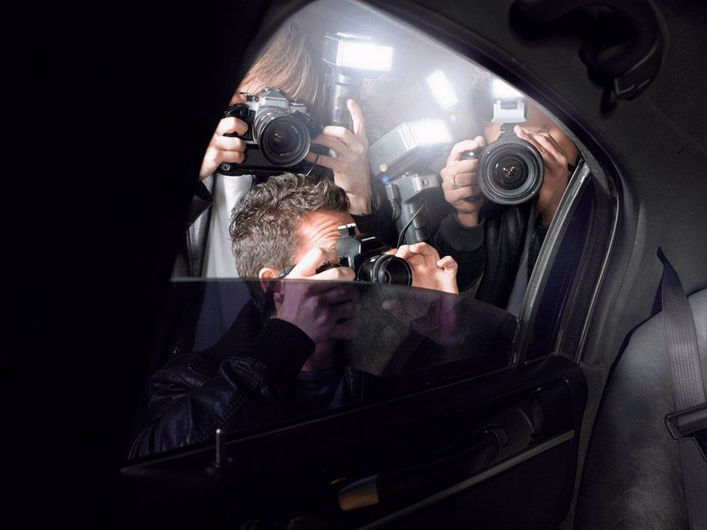 Paparazzi shooting through car window : Stock Photo