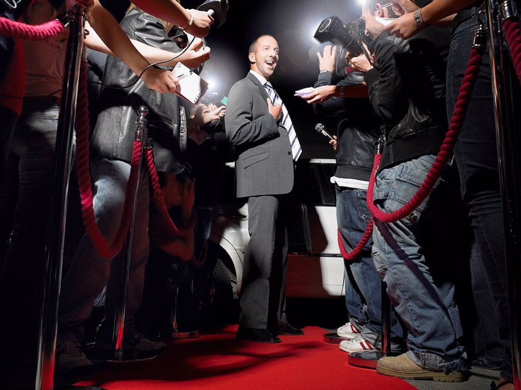 Stock Photo: 1654R-13387 Man on red carpet in front of paparazzi
