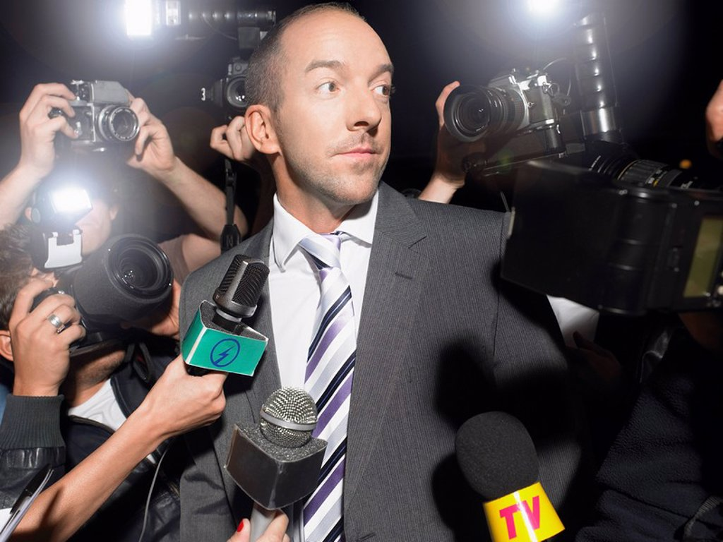 Stock Photo: 1654R-13389 Man surrounded by paparazzi