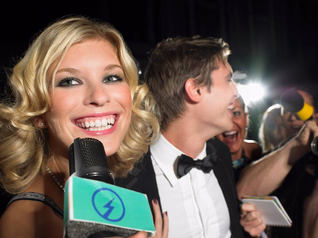 Woman talking into microphone man behind with paparazzi : Stock Photo
