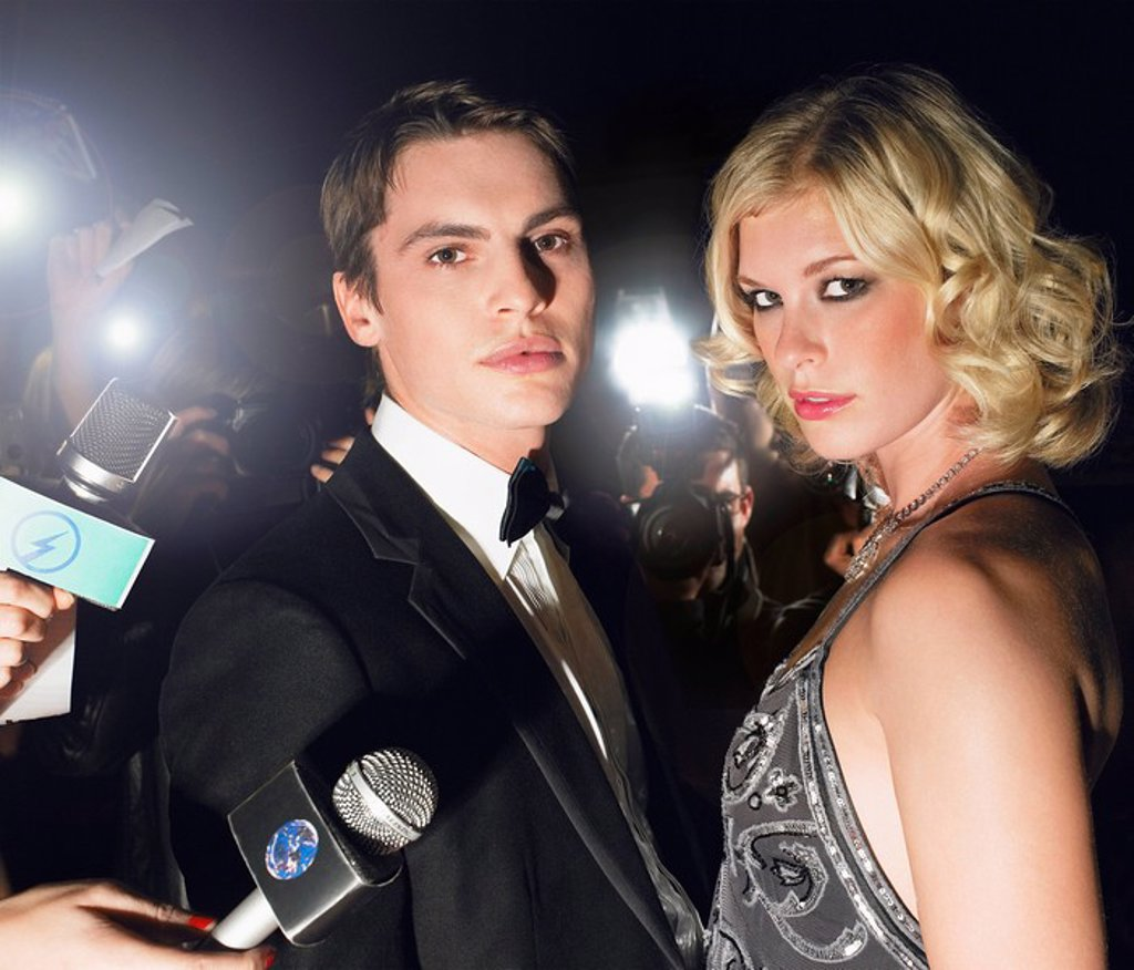 Couple posing in front of paparazzi : Stock Photo