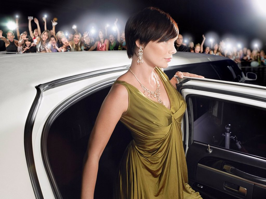 Woman in evening wear getting out of limousine in front of fans and paparazzi : Stock Photo