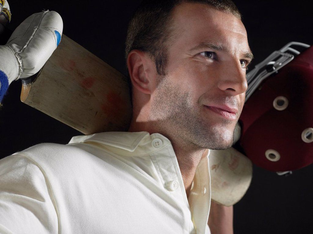 Cricket player holding cricket bat behind shoulders close_up : Stock Photo