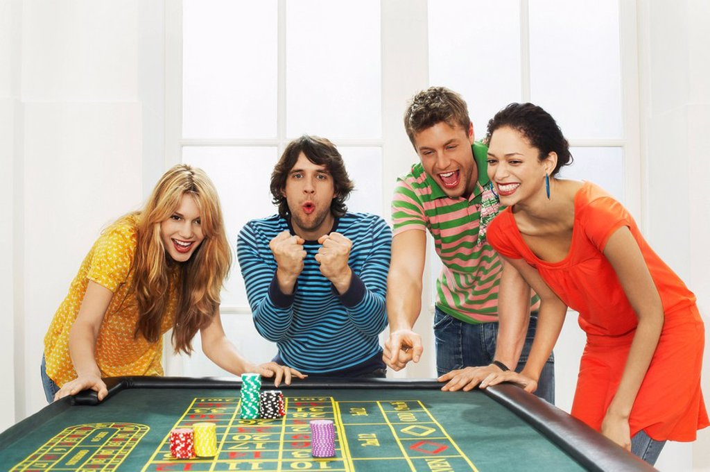 Friends celebrating win on roulette table : Stock Photo