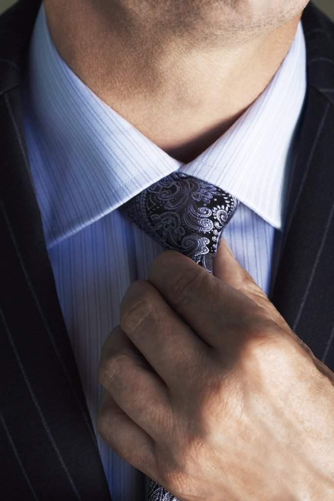 Businessman Adjusting Tie : Stock Photo
