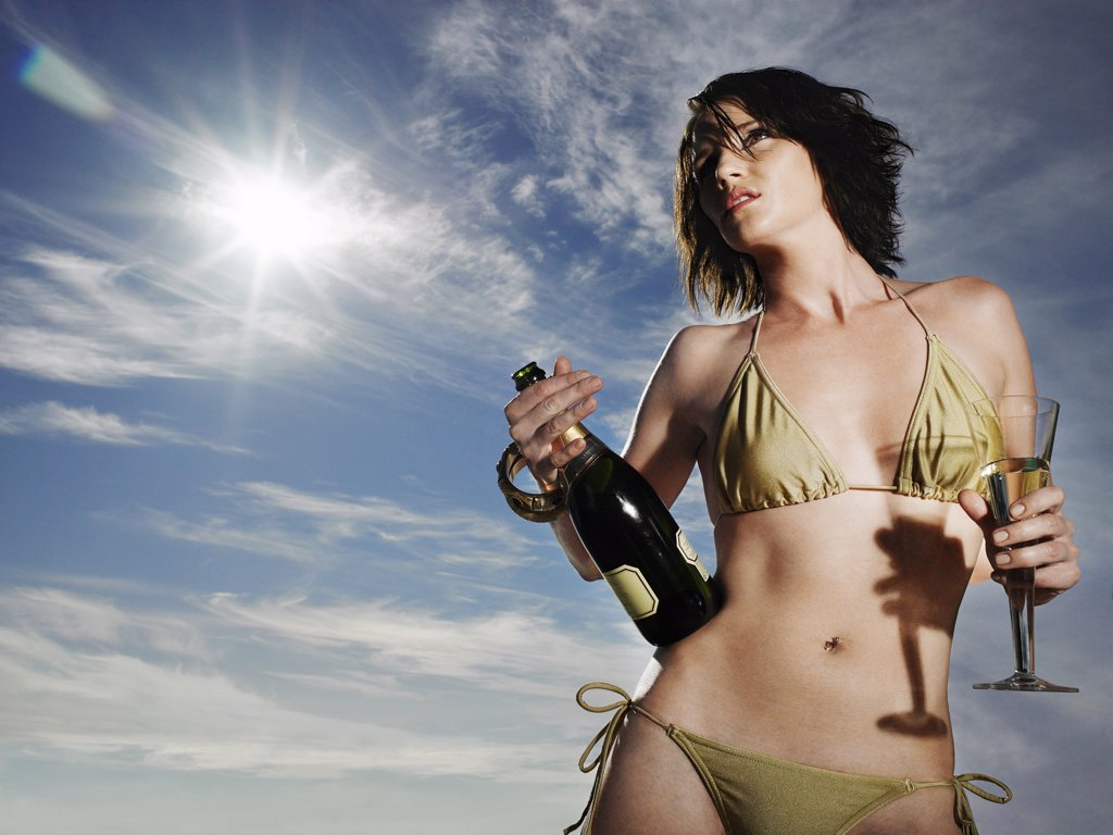 Woman in a Bikini Holding a Bottle of Champagne : Stock Photo