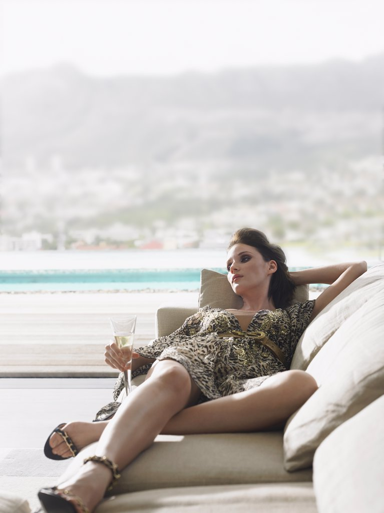 Woman Lying on a Sofa and Drinking Champagne : Stock Photo
