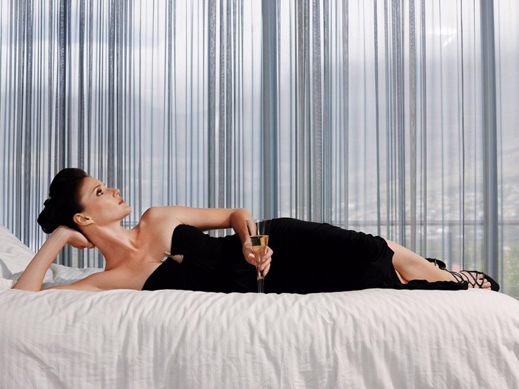 Woman wearing elegant dress lying on bed with champagne glass in bedroom : Stock Photo