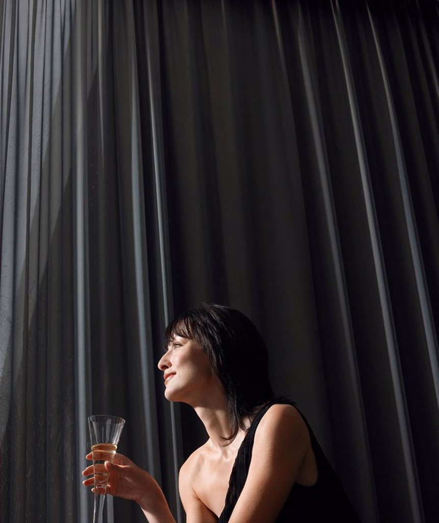 Woman holding champagne in front of curtains indoors : Stock Photo