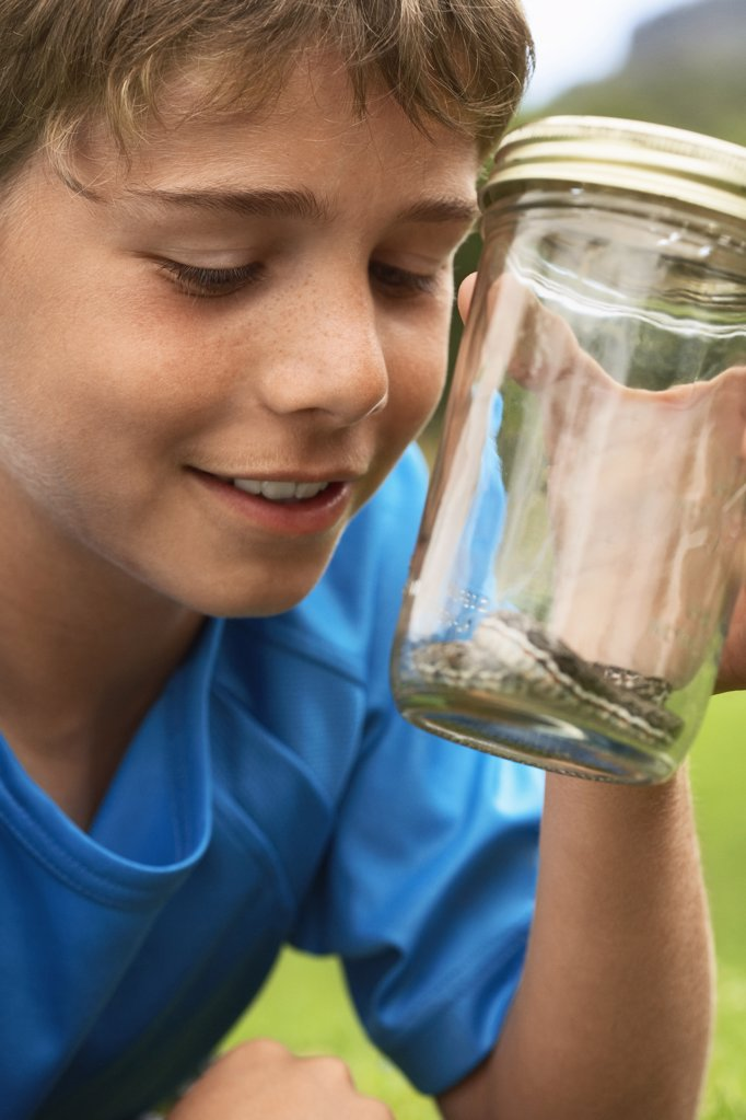 Boy Looking at Snake in Jar : Stock Photo
