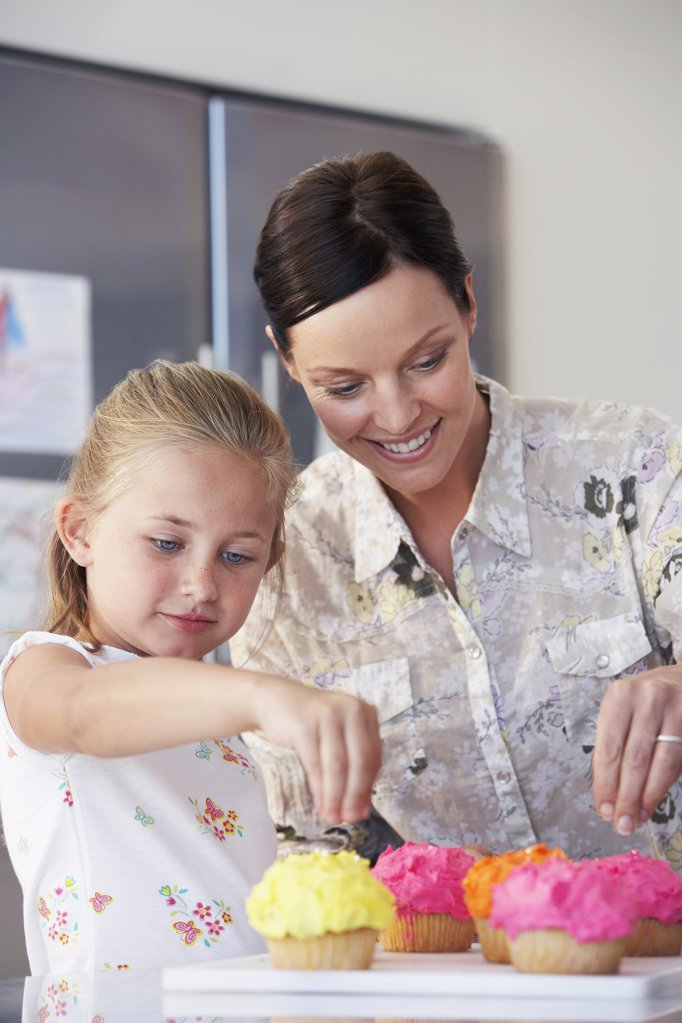 Stock Photo: 1654R-14666 Mother and Daughter Making Cupcakes