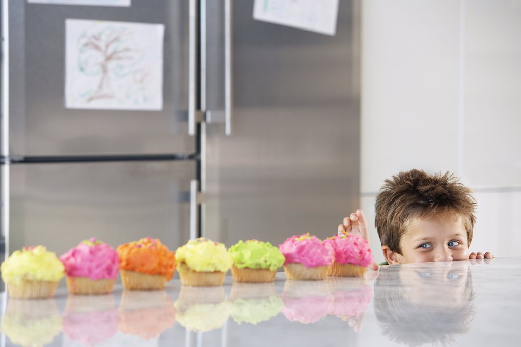 Little Boy Reaching for a Cupcake : Stock Photo
