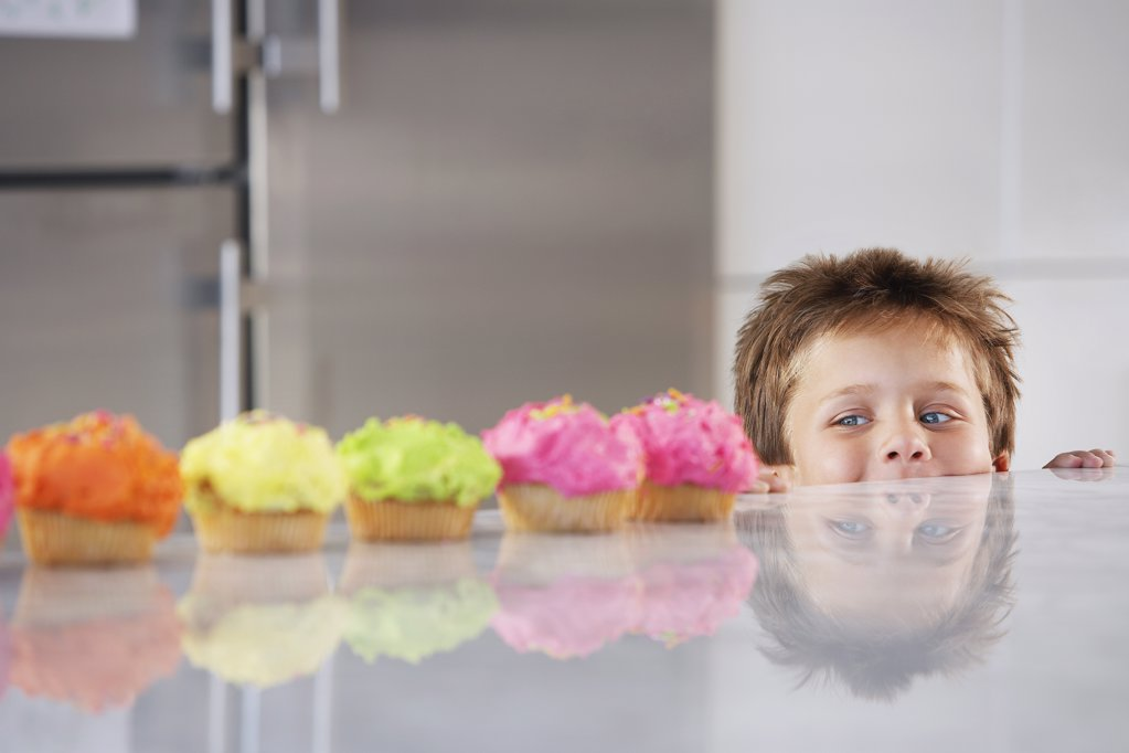 Little Boy Peeking at Cupcakes : Stock Photo