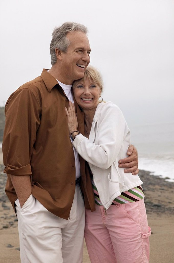 Stock Photo: 1654R-1484 Mature couple embracing on beach