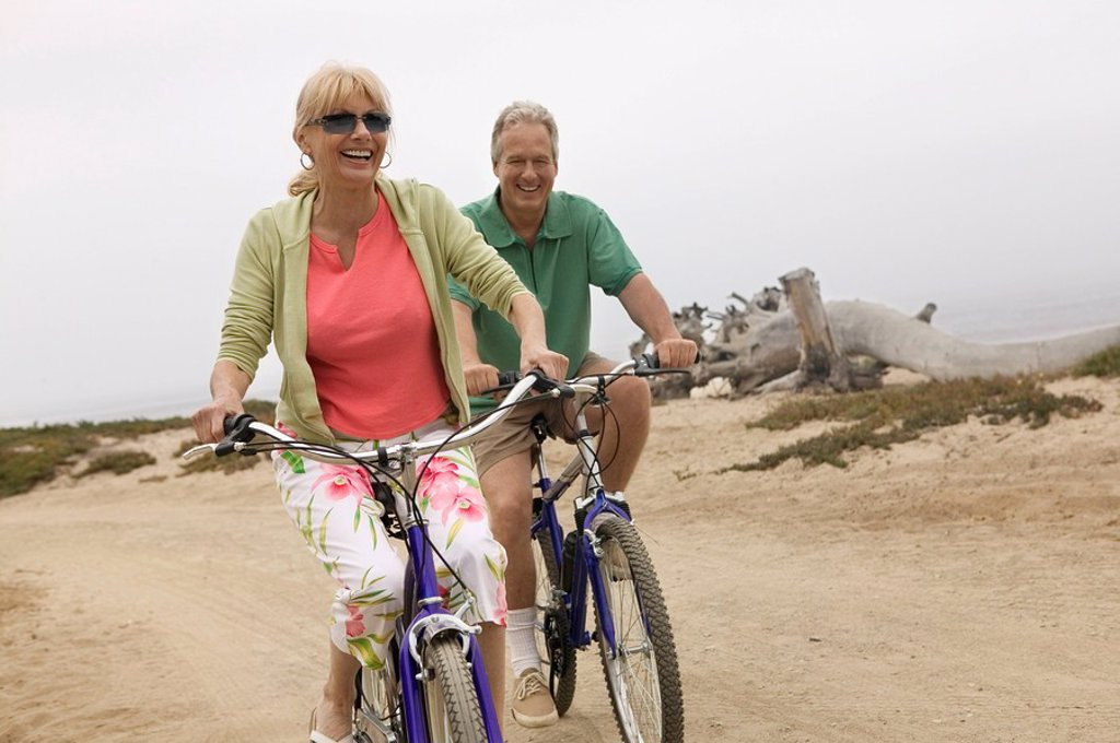 Stock Photo: 1654R-1490 Couple riding bicycles along beach