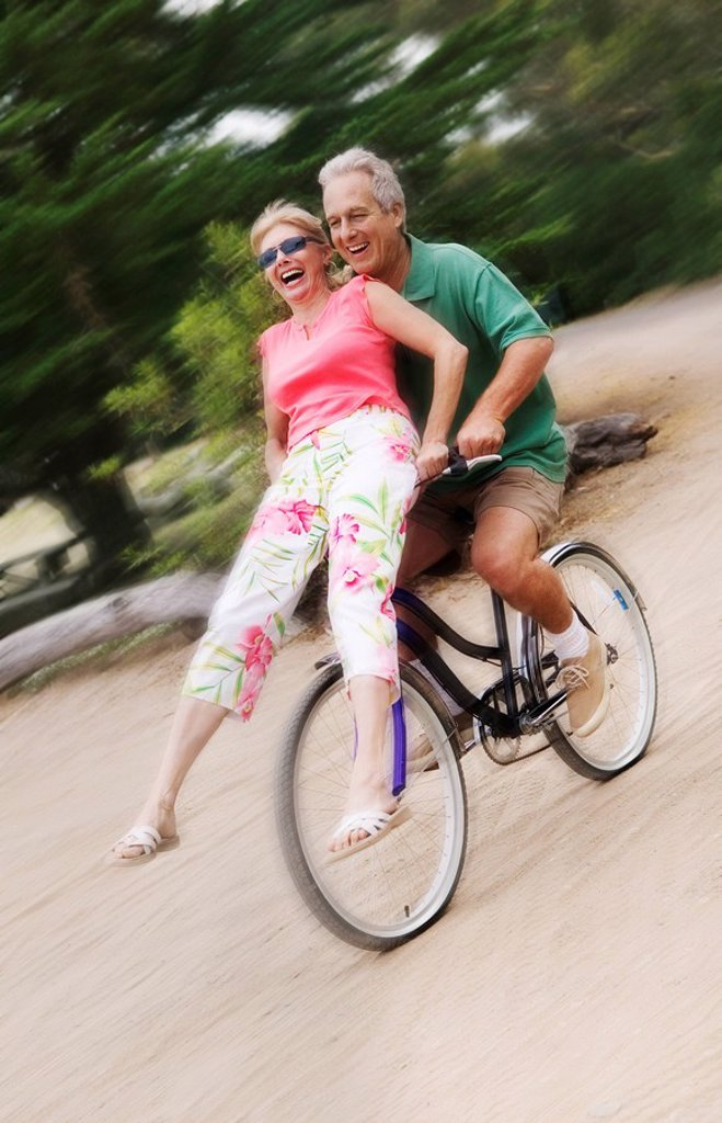 Stock Photo: 1654R-1491 Woman riding on handlebars of mans bicycle