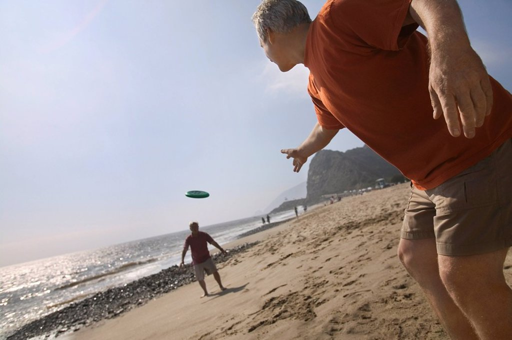 Two men playing with flying disc on beach : Stock Photo
