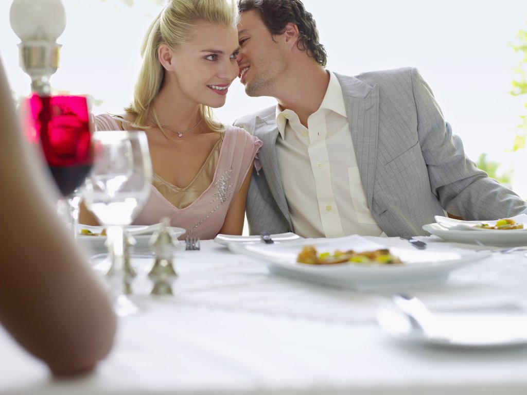 Stock Photo: 1654R-15192 Couple Whispering at Dinner