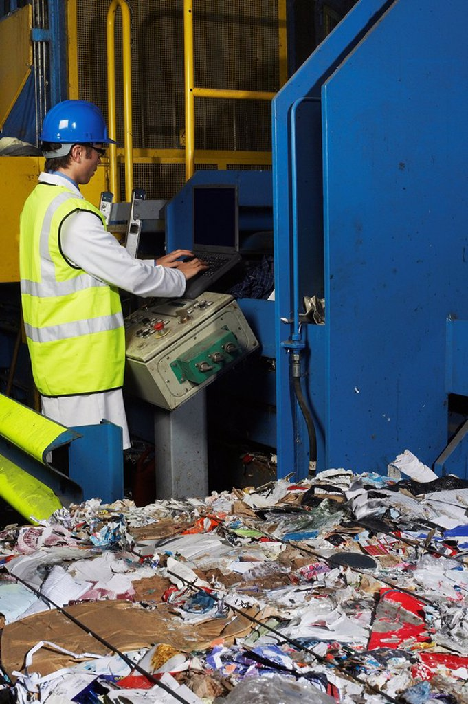 Stock Photo: 1654R-15311 Man operating conveyor belt in recycling factory side view