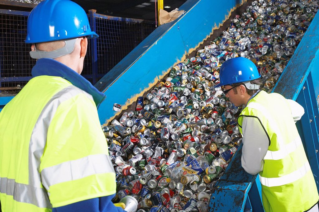 Two workers monitoring conveyor belt of recycled cans back view : Stock Photo