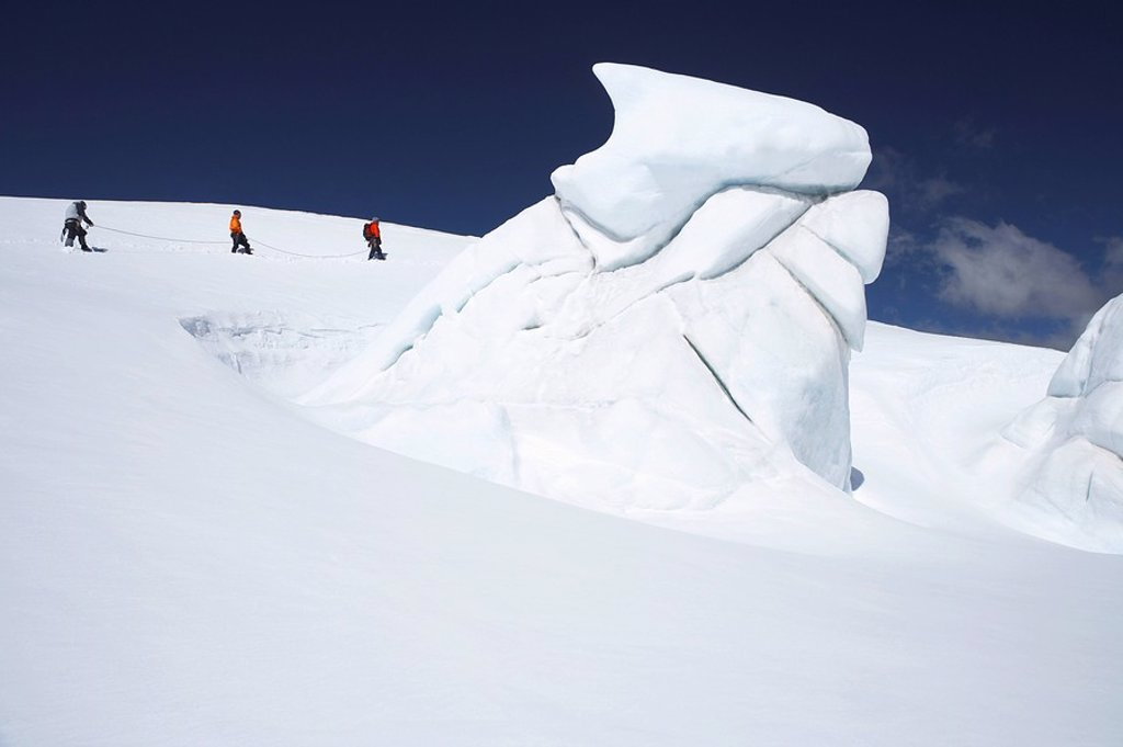 Mountain climbers walking past ice formation : Stock Photo