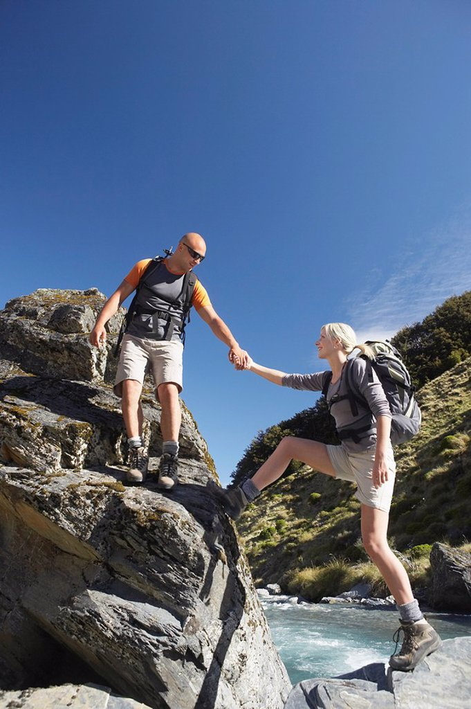 Stock Photo: 1654R-15503 Man helping woman climb onto boulder in middle of river