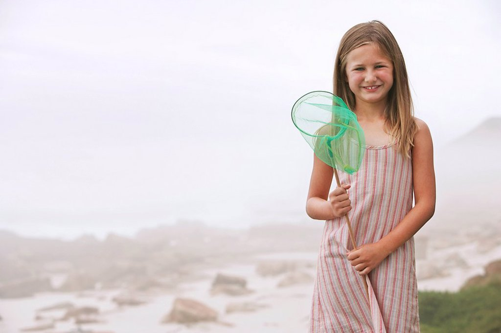 Girl 7_9 holding fishing net standing on beach portrait : Stock Photo