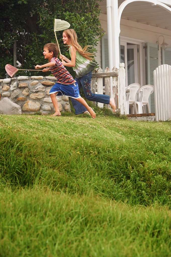 Brother and sister 5_6 10_12 holding fishing nets running in front of house : Stock Photo