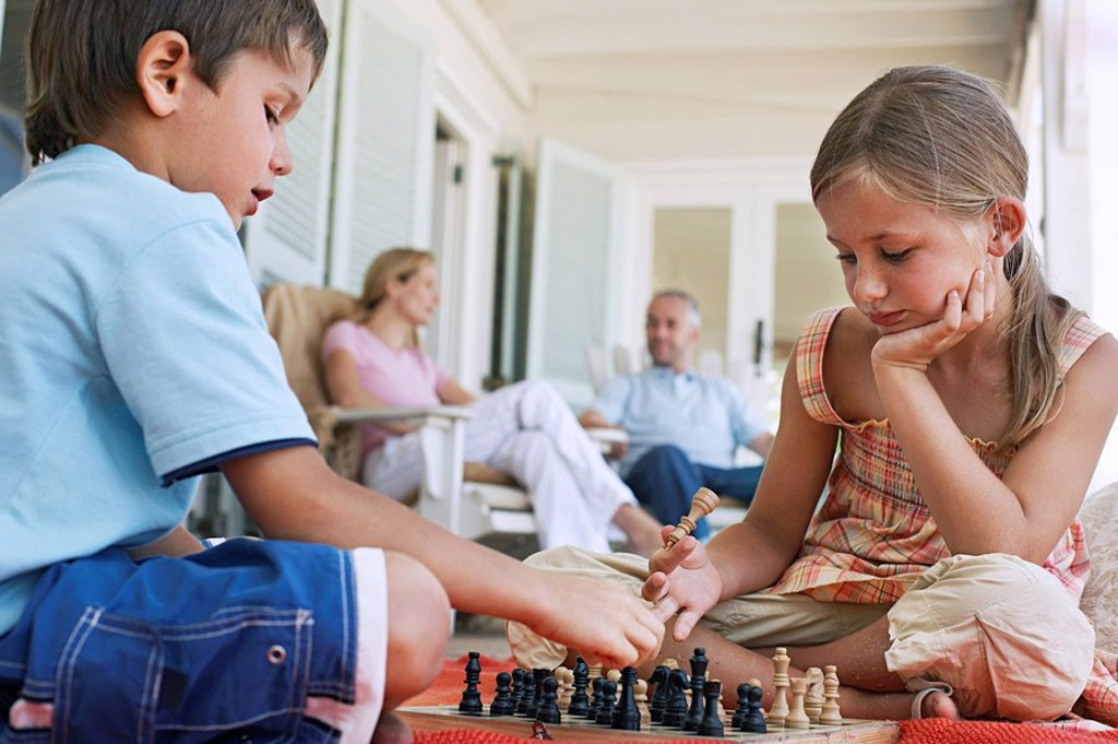 Brother and sister 7_9 playing chess on porch parents in background : Stock Photo