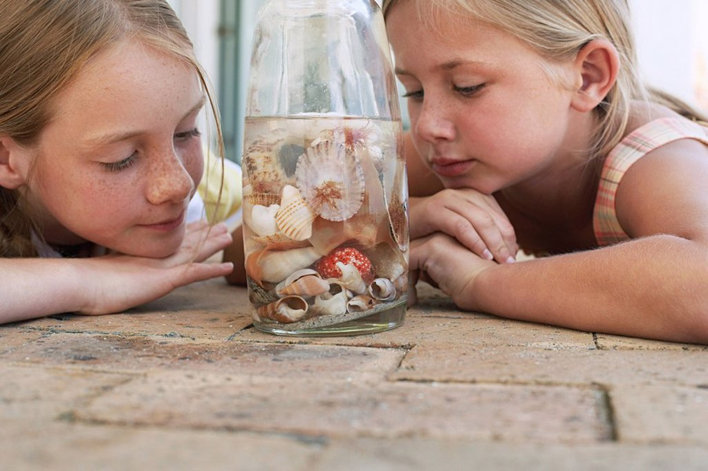 Two girls 7_9 10_12 looking at shells in jar close_up : Stock Photo