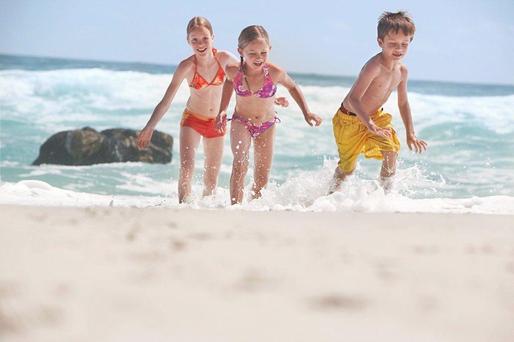 Three children 5_6 7_9 10_12 running on beach : Stock Photo