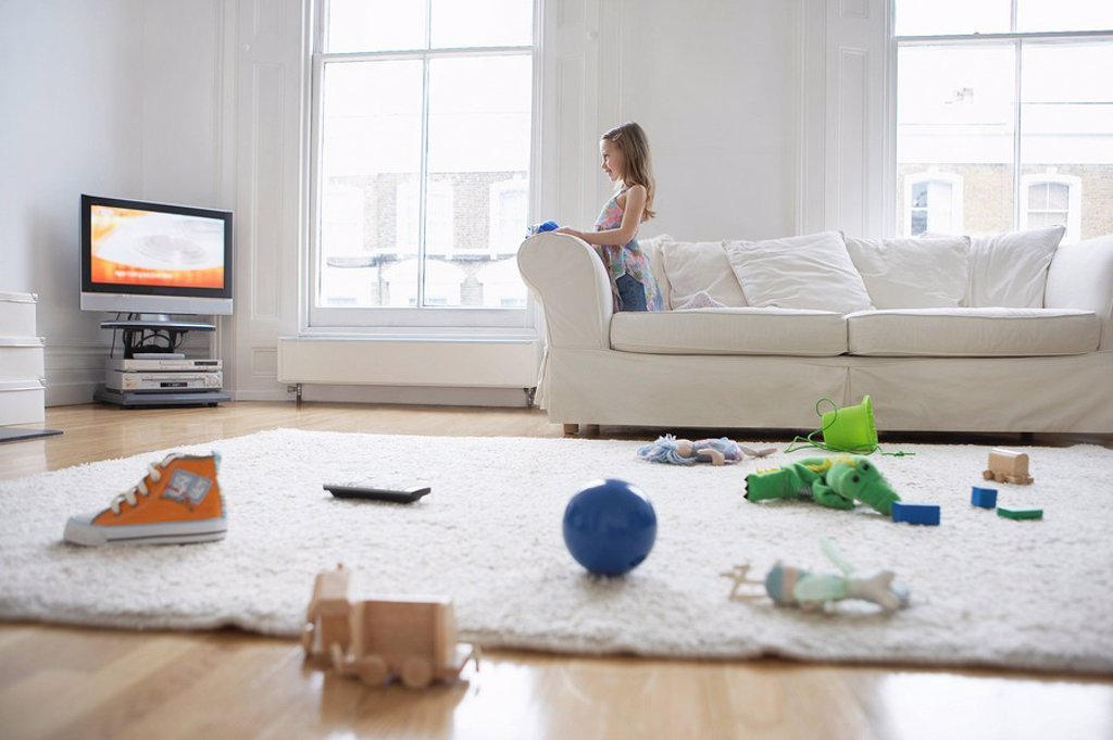 Girl 5_6 watching television toys on floor in foreground : Stock Photo