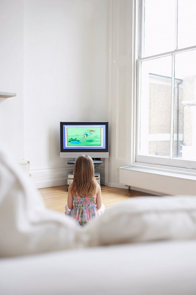 Girl 5_6 watching cartoons in television back view : Stock Photo