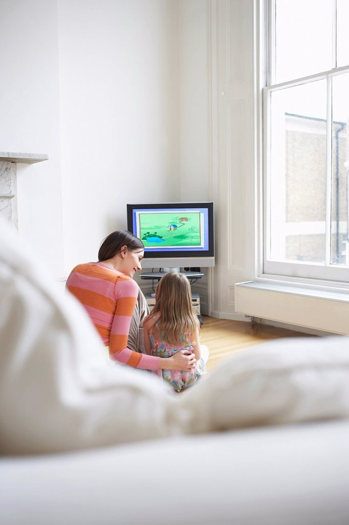 Mother and daughter 5_6 watching cartoons in television back view : Stock Photo