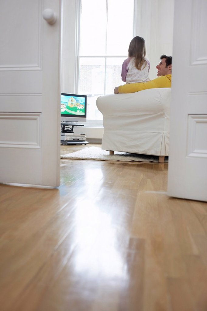 Stock Photo: 1654R-15737 Father and daughter 5_6 watching cartoons in television back view