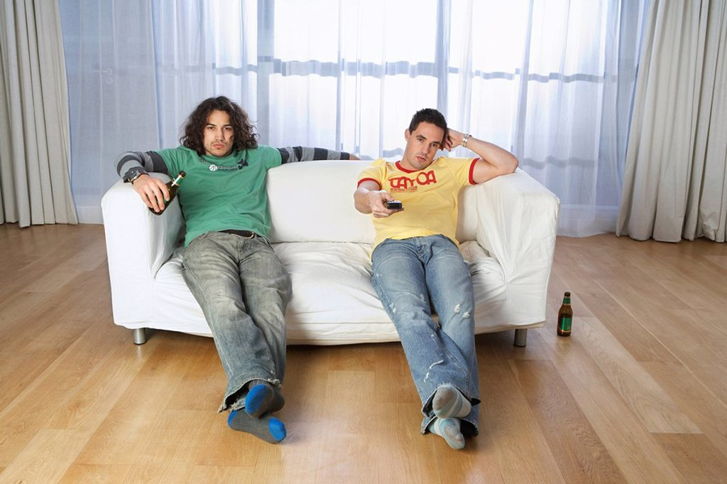Two men sitting on sofa watching television : Stock Photo