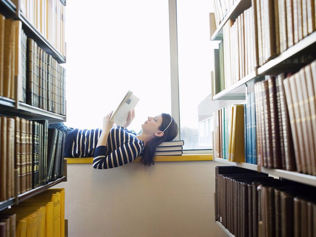 Stock Photo: 1654R-15775 Student lying down on windowsill in library reading