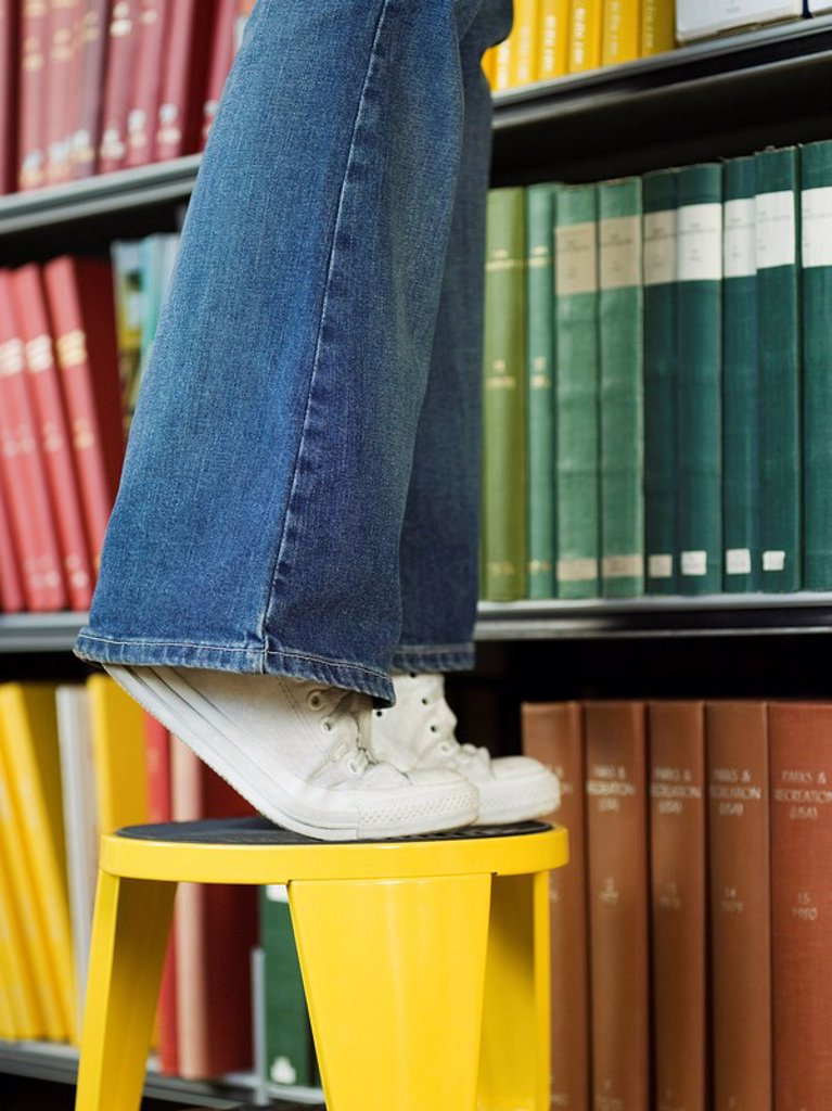 Young woman standing on stool reaching for book low section : Stock Photo