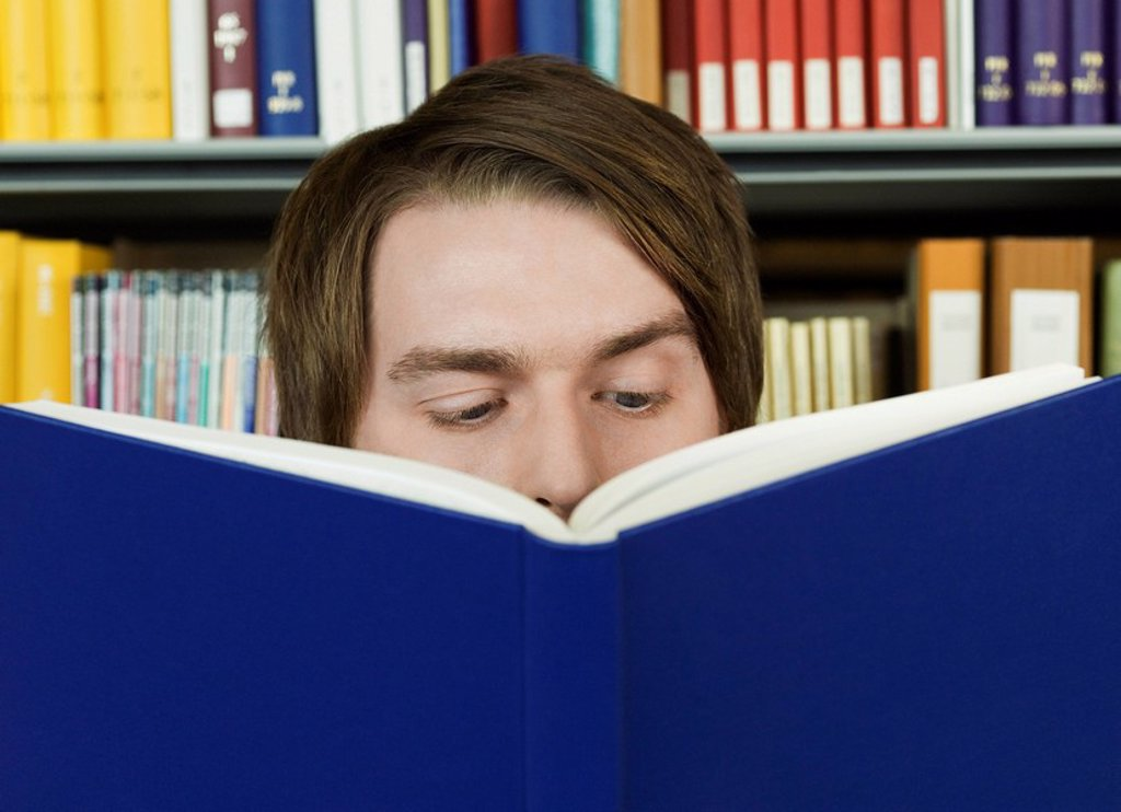 Young man reading : Stock Photo