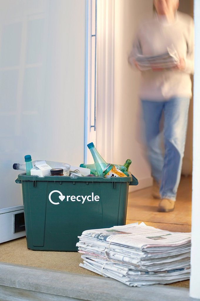 Recycling container and pile of waste paper on floor woman walking in background motion blur : Stock Photo