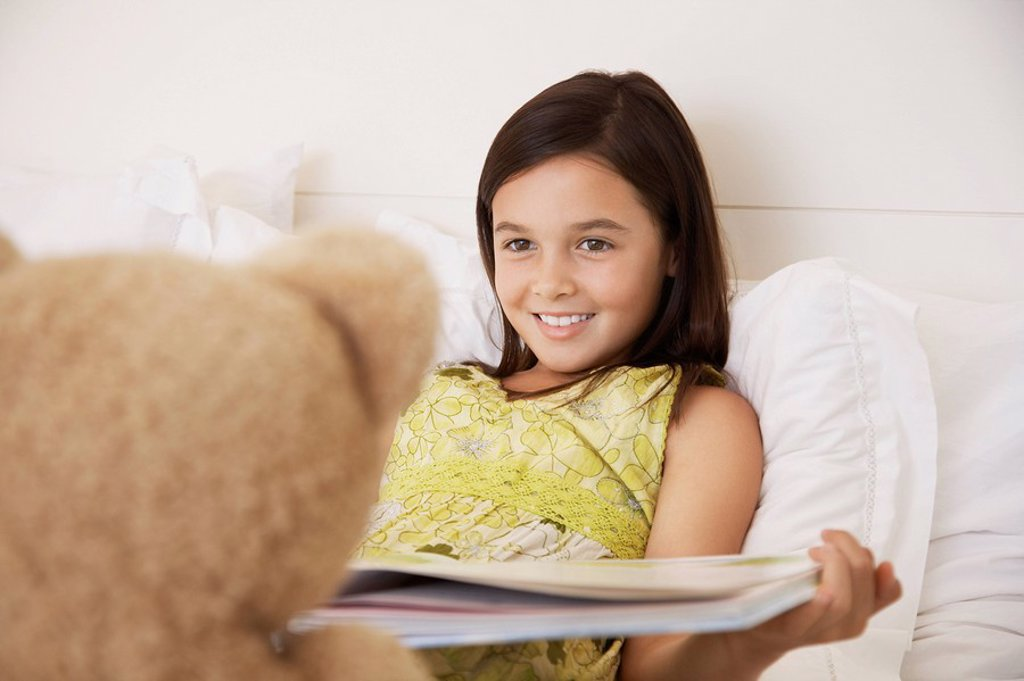 Girl reading story to teddy bear sitting on bed : Stock Photo