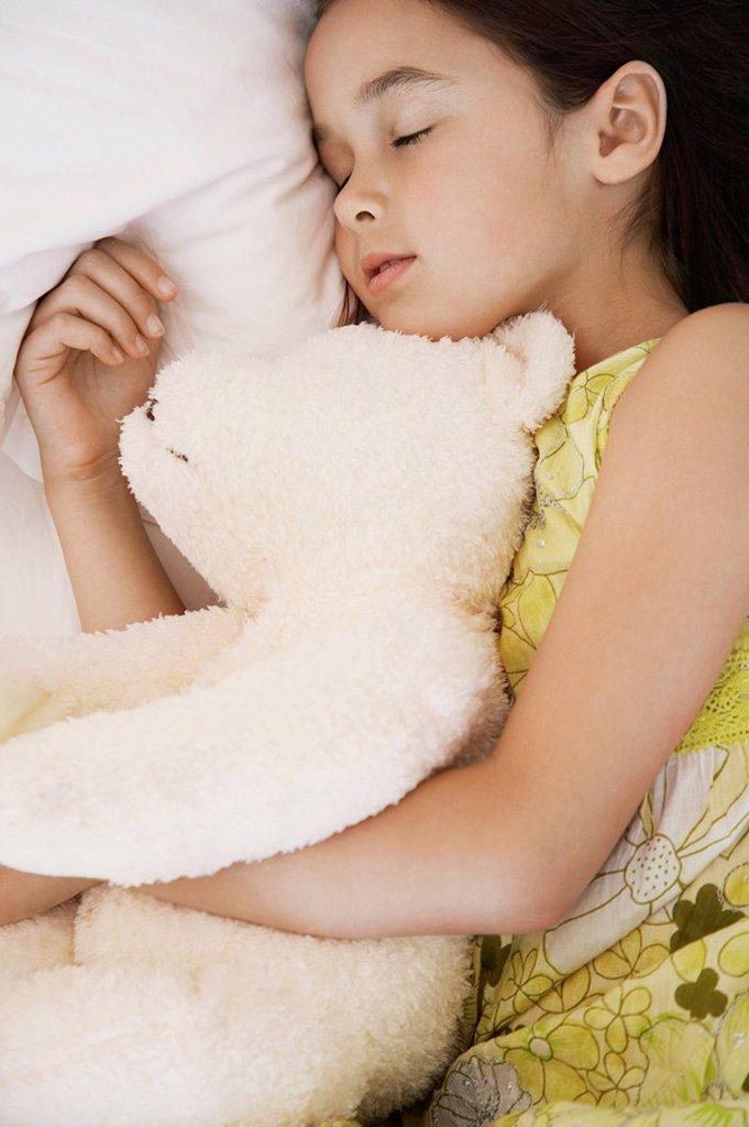Stock Photo: 1654R-16373 Girl cuddling teddy asleep on bed